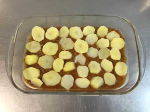 Primeira camada: molho bolonhesa e batatas fatiadas